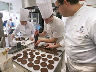 Students prepare chocolate cakes as they attend a pastry class at the Institut Paul Bocuse, in a 19th century chateau, in Ecully near Lyon