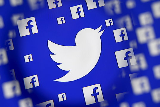 Logo of the Twitter and Facebook are seen through magnifier on display in this illustration taken in Sarajevo