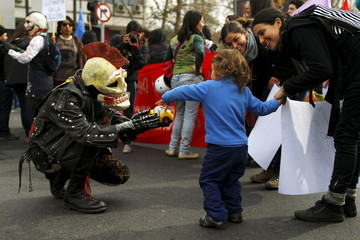 Demonstrator wearing a skull mask gives a toy car to a child during a rally held to support women's rights to an abortion