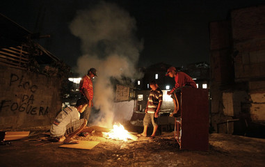Youths warm themselves by a bonfire in the Vila Flavia favela of Sao Paulo