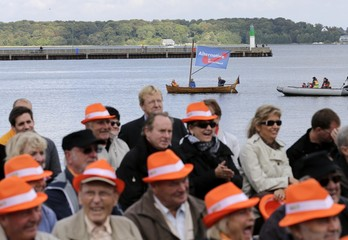 Supporters of AfD sail a boat next to square where German Chancellor Merkel smiles during a CDU election campaign rally in Stralsund