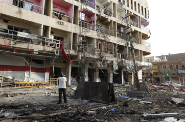 A man inspects the site of a car bomb attack in Baghdad