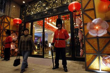 A visitor walks out of a hotel with attendants dressed as members of the Queen's Guard in Macau