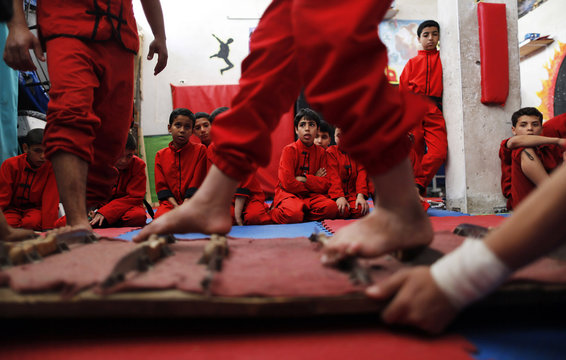 Palestinian boys watch as others stand on knifes during a class at the Red Dragon martial arts club in Beit Lahiya in the northern Gaza Strip