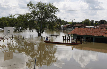 Residents use a canoe to navigate through a flooded street in the municipality of Yotoco, Valle del Cauca department