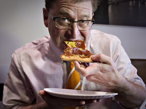 British Columbia's New Democrat Party leader Adrian Dix eats pizza while campaigning in Vancouver