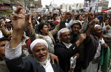 Anti-government protesters shout slogans during a rally outside Sanaa University