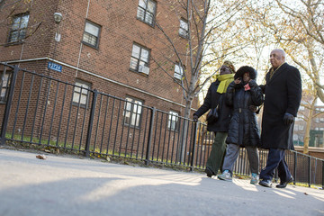 "Assemblyman Barron, his wife City Councilwoman Barron and area resident Butler walk outside of a public housing project in Brooklyn known as the ""Pink Houses"", where Gurley was killed by what the NYPD is saying could be an accidental discharge in New York"