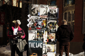 Pedestrians look at posters advertising movies along Main St. during the Sundance Film Festival in Park City, Utah