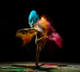 Girl dancing in a cloud of color dust studio portrait