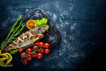 Trout fish baked with aromatic herbs and spices. On Wooden background.