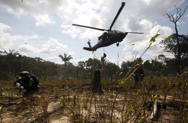 A Colombian anti-drug policeman rappel from a Black Hawk helicopter during an anti-drug operation at a cocaine laboratory in Puerto Concordia