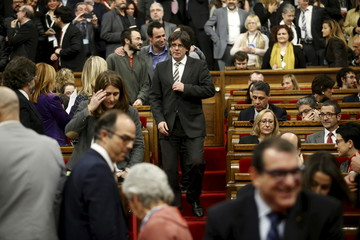 Incoming Catalan President Puigdemont adjusts his jacket during the investiture session at the Catalunya Parliament in Barcelona