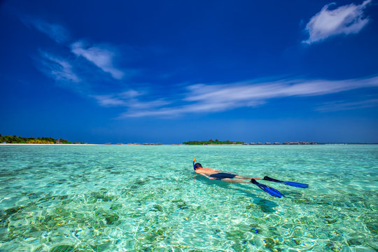 Young man snorkling in tropical lagoon with over water bungalows, Maldives