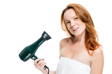 Horizontal portrait of a red-haired woman with a hairdryer on a white background isolated