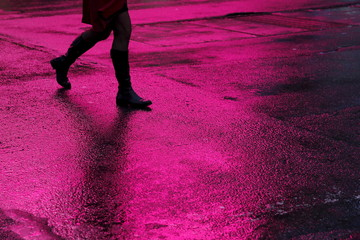A woman walks in silhouette across a rain soaked 7th avenue in New York