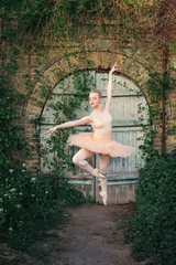 Young woman with perfect body in white tutu dancing outdoors with urban background. Beautiful ballerina showing classic ballet poses and jumping high into the air