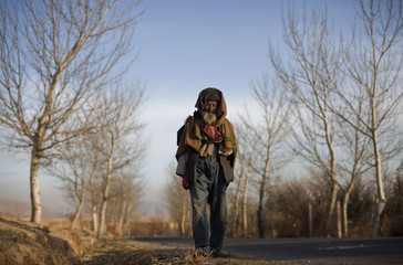 An Afghan elderly man heads home at the end of a day, in Kabul
