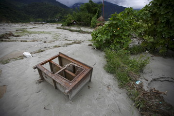 A kitchen cabinet, washed away by a flood due to heavy rainfall, lies on a riverbank in Kaski District