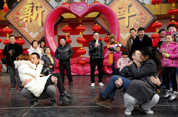 People look at couples participating in a kissing contest held in celebration of Valentine's Day at the Happy Valley amusement park in Beijing