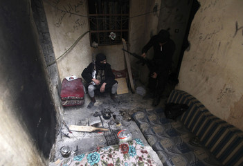 Free Syrian Army fighters carry their weapons as they take positions inside a building in Deir al-Zor, eastern Syria