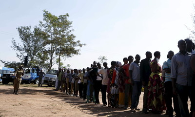 A policeman watches as voters queue at a polling station during the presidential elections in Kirihura in western Uganda