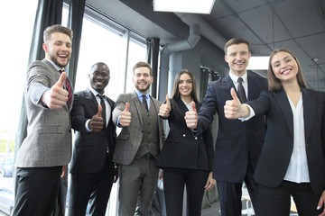Portrait of happy businesspeople standing in office showing thumb up.
