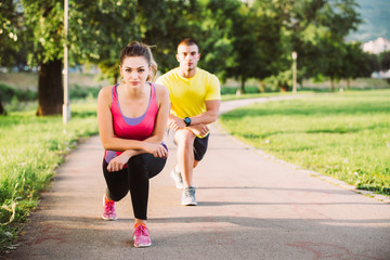 Couple stretching before jogging at the bench in the park