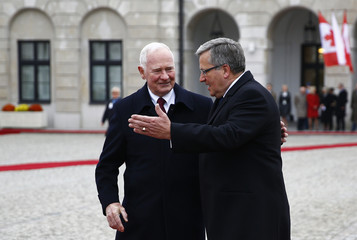 Poland's President Komorowski gestures as he meets with Canda's Governor General Johnston during a welcoming ceremony at the courtyard of the Presidential Palace in Warsaw