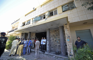 Security personnel and residents gather at the scene of a car bomb explosion at the Swedish consulate in Benghazi