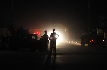Afghan policemen keep watch at the site of an attack in Kabul