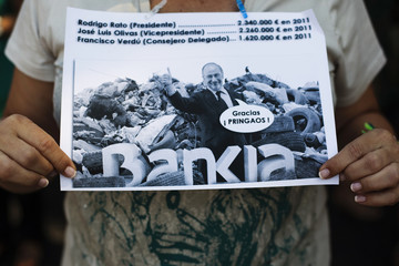 A civil servant holds an image of former chairman of Spain's Bankia Rato superimposed against the background of a rubbish dump during a protest against government austerity measures in Madrid