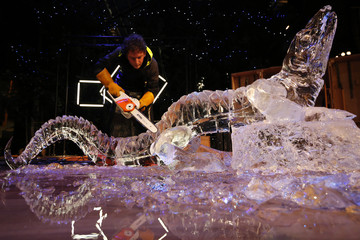 "An artist from the company ""La Machine"" uses an electric chain saw to complete a  performance where they created an ice sculpture in the form of a lizard, in Nantes"