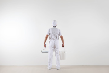 Rear view of painter man looking at blank wall, with paint roller and bucket, isolated on white room