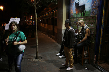 People hang out outside a bar displaying a bull on the wall as a demonstrator walks as protesters try to surround Madrid's Parliament as the debate for the 2013 budget goes on inside
