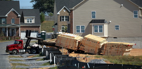 Lumber on pallets for framing new house construction are unloaded at a large subdivision in Damascus