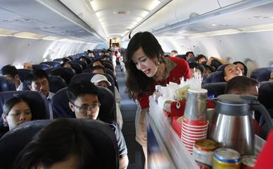 A Vietjet Air flight attendant serves passengers during a flight from Ho Chi Minh city to Hanoi