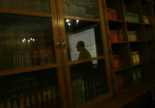 A man is reflected in a bookcase as he views a demonstration of Google Map Maker during its UK launch in Bletchley
