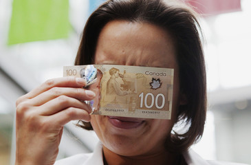 Warren demonstrates how to view a security feature on the new polymer Canadian 100 dollar bill to reveal hidden numbers in Toronto