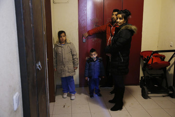 Montoya Vazquez's daughter-in-law Santa Navarro, her husband and two of their three children react as they look at the welded door blocking the entrance to their former home after getting evicted in Madrid