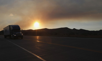 A truck drives down the highway under the smoke plume from the High Park fire at sunset, west of Fort Collins