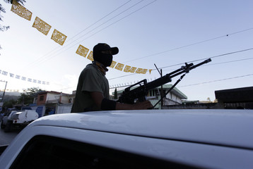 A member of the community police of Guerrero keeps watch on the bed of a pick up truck as they march to demand the safe return of the missing 43 students of the Ayotzinapa Teacher Training College, in Tixtla