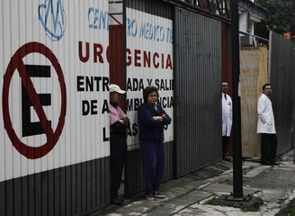 Hospital employees wait outside their building after an earthquake, in Mexico City