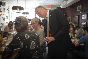 New York Mayor Bill de Blasio speaks to a customer at The Meatball Shop as he arrives to have lunch there in New York