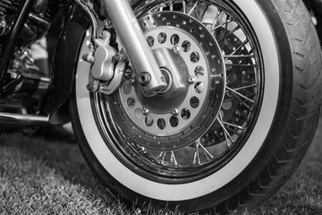 Front wheel of Vintage Motorcycle photographed outdoors. Black and white photo.