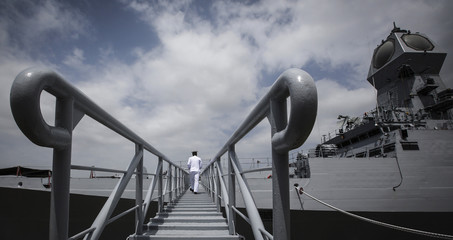 An Indian navy serviceman boards the newly commissioned warship, INS Kolkata, during its commissioning ceremony at a naval base in Mumbai