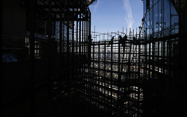 Construction workers are silhouetted while standing on a scaffolding at the construction site of the new headquarters of the European Central Bank (ECB) during a guided media tour in Frankfurt