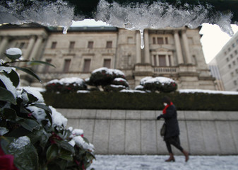 Woman walks past BOJ headquarters covered with snow in Tokyo