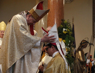 Cardinal Koch puts the hat on new Bishop Gmuer of the diocese Basel during his ordination as bishop in Olten
