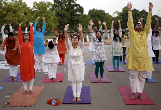 """Participants perform a """"Surya Namaskar"""" during an early morning yoga session ahead of World Yoga Day, in New Delhi, India"""